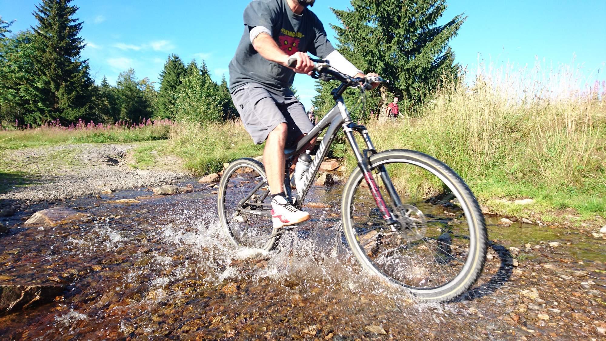 Obrázek cyklisty na kole projíždějící potokem